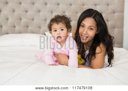 Brunette playing with her baby and a duck on the bed