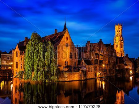 Famous view of Bruges-  Belfry and old houses along canal with tree. Brugge, Belgium