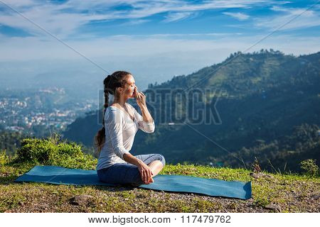 Woman practices pranayama yoga breath control in lotus pose padmasana outdoors in Himalayas in the morning on sunrise. Himachal Pradesh, India