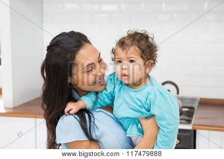 Smiling brunette holding her baby in the kitchen