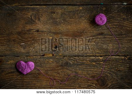 Purple Heart With A Ball Of Thread On On Old Shabby Wooden Background