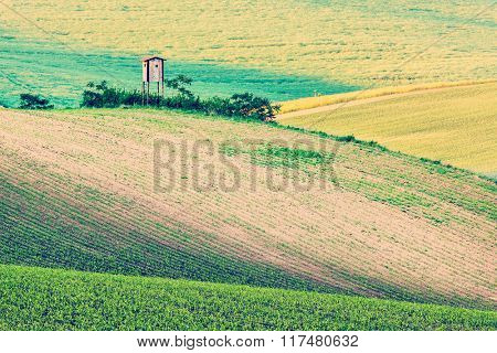 Vintage retro effect filtered hipster style image of Rural Europe background - Moravian rolling landscape with hunting tower shack on sunset. Moravia, Czech Republic