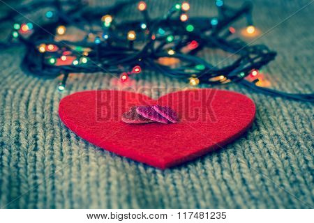Small Decorative Hearts On A Red Felt Heart And Colorful Garland