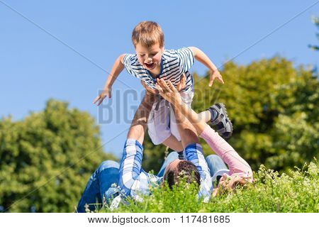 Family playing with son lying in grass on meadow
