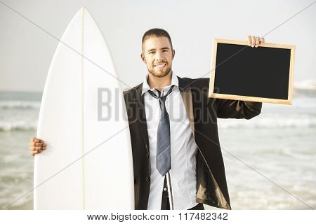 Businessman holding a chalkboard and is surfboard. Concept about a man starting a new life.