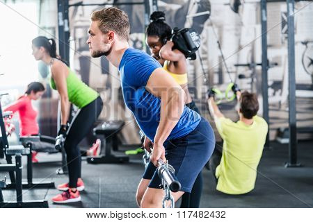 People exercising in functional fitness gym, group of women and men