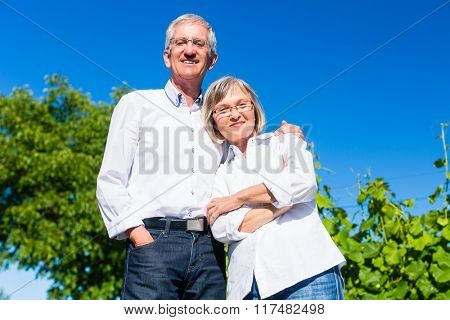 Senior woman and man embracing each other in summer
