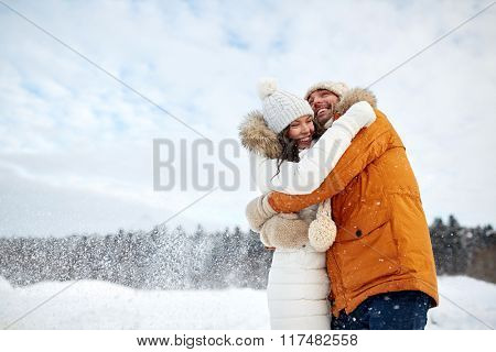 people, season, love and leisure concept - happy couple hugging outdoors in winter