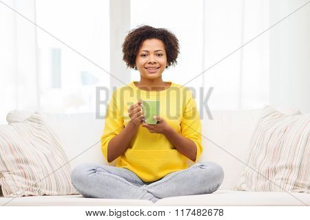 people, drinks and leisure concept - happy african american woman sitting on sofa and drinking tea from cup or mug at home