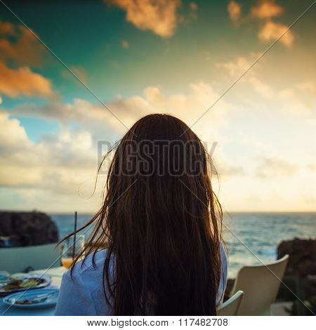 Woman enjoying sunset at the ocean in her vacation sitting in restaurant, filtered image