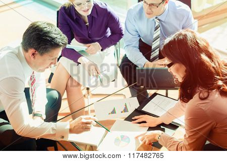 Team of women and men working in office discussing documents