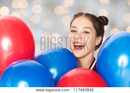 people, teens, holidays and party concept - happy smiling pretty teenage girl with helium balloons over holidays lights background