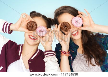 people, friends, teens and friendship concept - happy smiling pretty teenage girls with donuts making faces and having fun over blue background
