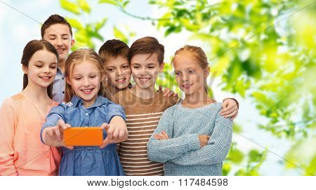 childhood, friendship, technology and people concept - happy children talking selfie by smartphone over green natural background