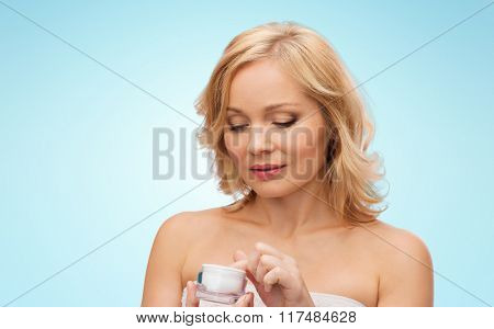 beauty, people, skincare and cosmetics concept - middle aged woman with cream jar over blue background