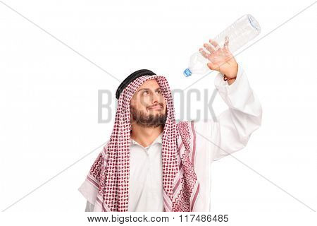Studio shot of a thirsty young Arab holding an empty plastic bottle isolated on white background
