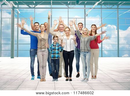 travel, vacation and people concept - group of happy people or big family waving hands over airport terminal window and sky background