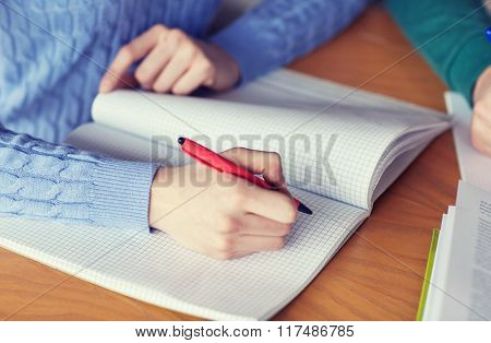 people, learning, education and high school concept - close up of female student hands writing to notebook