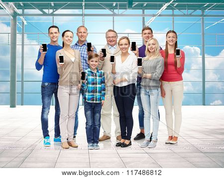 travel, vacation and people concept - group of happy people or big family showing smartphones over airport terminal window and sky background