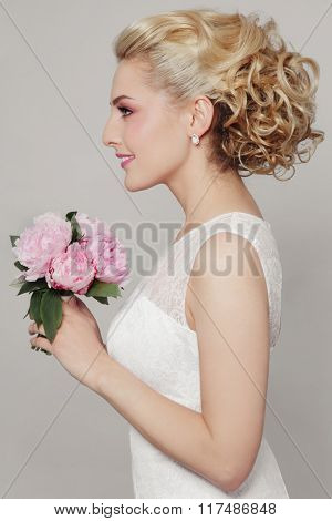 Young beautiful blonde slim bride with stylish prom hairdo and bridal bouquet
