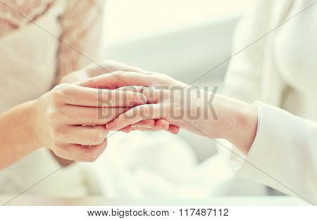 people, homosexuality, same-sex marriage and love concept - close up of happy lesbian couple hands putting on wedding ring