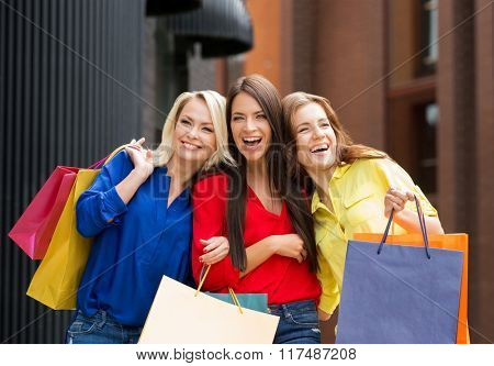 Three beautiful young women laughing and being very emotional after shopping.