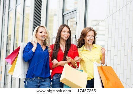 Three attractive happy female friends walking in the city center with shopping bags along showcases.