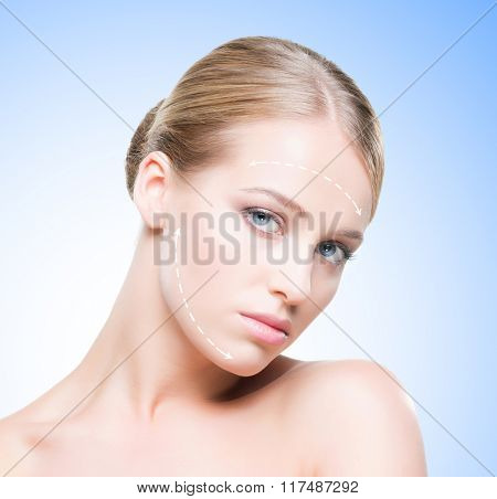 Portrait of beautiful and healthy woman with arrows on her face. Beauty, medicine, plastic surgery and skin care concept.