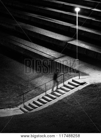 Double exposure night scene. Human figure in motion blur walking up stairs.