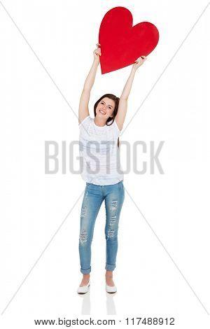 cheerful teen girl holding heart shape on white background