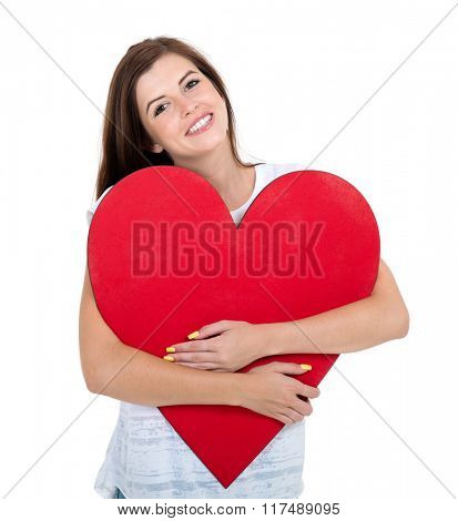 cheerful teen girl hugging red heart isolated on white