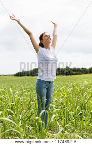 beautiful carefree young girl arms open in sugarcane field