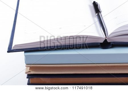 Close-up of open book and pen