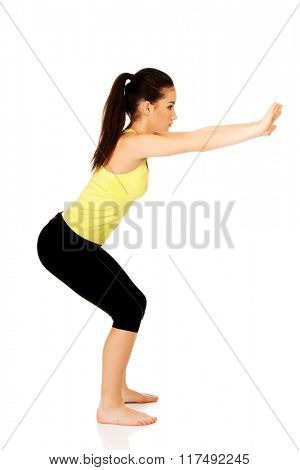 Young woman performs squats.