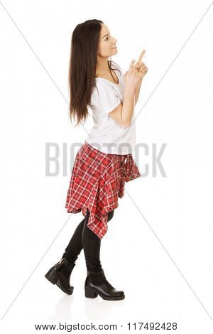 Young rock woman pointing up.