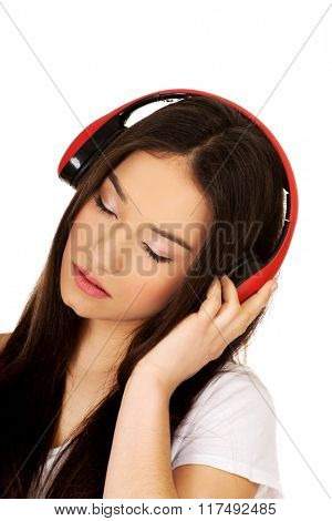 Rock woman with headphones listening to music.