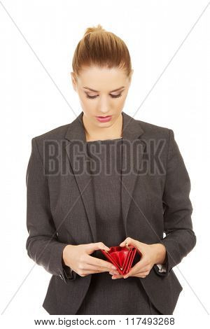 Unhappy woman looking into her wallet.