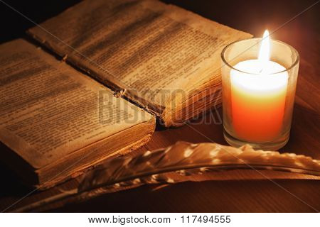 Open Old Book In The Light Of A Candle