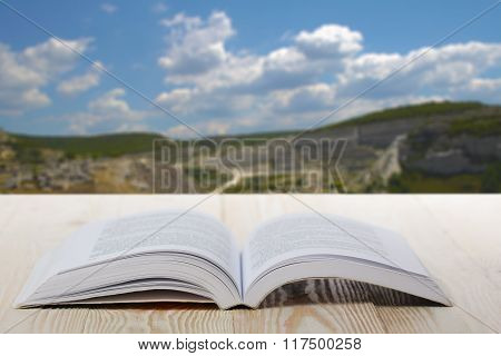 Open book at wooden table on natural blurred background