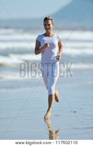 young athletic woman jogging on the beach in summer sunny day