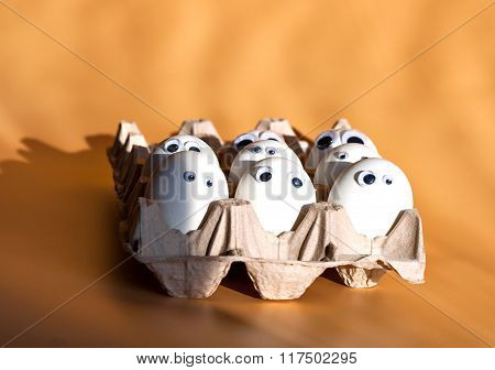 Group of eggs with false eyes in a cardboard container. Breakfast