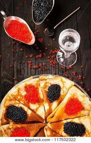 A glass of vodka, red and black caviar and pancakes on a wooden background