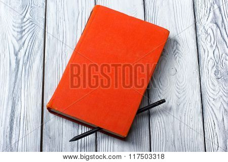 Blank red hardcover book with black pencil on white wooden background.