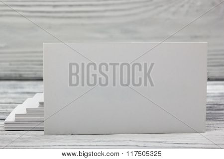 Blank white business cards on wood background