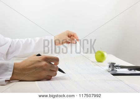 Healthcare and medicine concept - doctor with medical clipboard, green apple analyzing cardiogram.