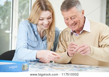 Teenage Granddaughter Helping Grandfather With Jigsaw Puzzle