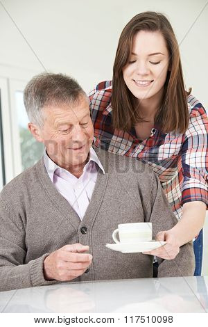 Teenage Granddaughter Bringing Grandfather Hot Drink