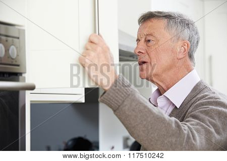 Forgetful Senior Man Looking In Cupboard