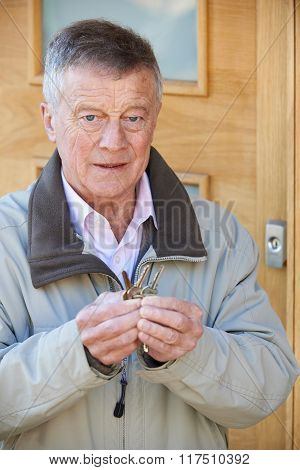 Confused Senior Man Trying To Find Door Key