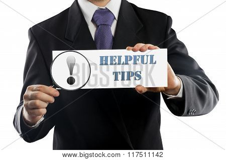 Close up businessman or salesman holding in hands magnifying glass and paper with Helpful Tips messa